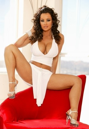 Sexy MILF Lisa Ann exposes her big boobs and bare ass on a red chair
