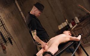 Nude female on a bondage rack has her pussy masturbated against her will