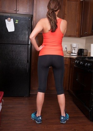 Fit MILF removes her spandex capris to masturbate barefoot in the kitchen