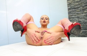 Blonde model Ivana Sugar poses in fishnet stockings and high heeled shoes