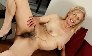 Mature blonde woman holds her floppy boobs while she fingers her hairy bush