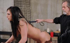 Nude brunette female grimaces as she gets caned and flogged