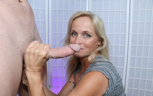 Clothed older woman Dani Dare jerks off a long dick until it blows a load