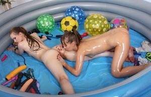 Oiled up dykes toy each others assholes with a double ended dildo