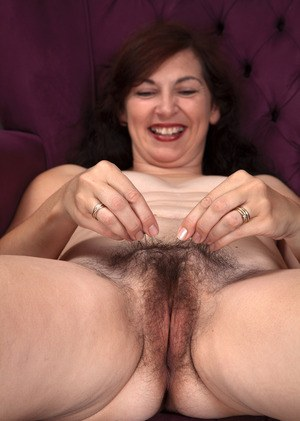 Petite mature lady hikes up her dress and shows off her hairy snatch