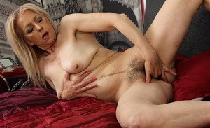 Older lady removes her dress and pretties before finger fucking her hairy bush