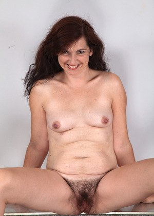 Mature woman spreads her hairy bush wide open after she gets naked