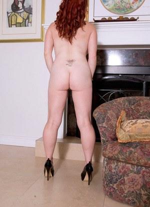 Redhead solo model Red Vixen sets her huge tits free as she strips naked