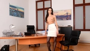 Middle-aged secretary Linda Moretti takes off her glasses prior to stripping