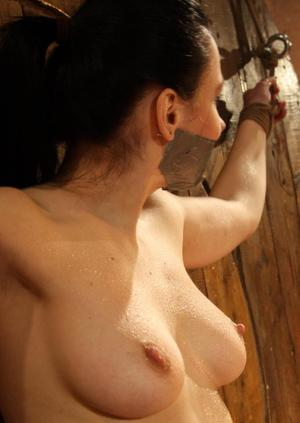 Topless brunette is left chained to a wall with duct tape covering her mouth