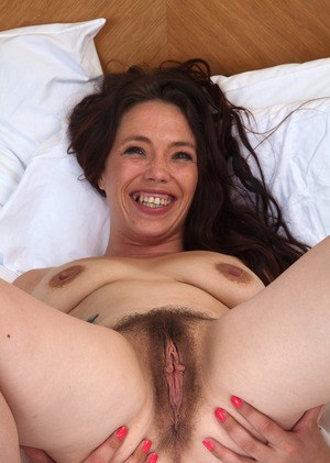 Middle-aged brunette woman is all smiles showing off her hairy muff