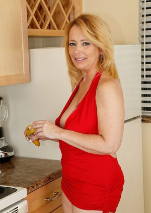 Mature woman Brandie Sweet doffs her red dress and heels to pose in the nude