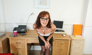 Mature lady Georgie takes off her glasses and then her clothes in home office