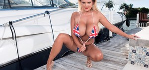 Blonde bombshell Katie Thornton slips off her UK themed bikini on boat dock