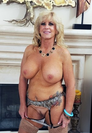 Older lady Zena Rey strips down to nylons and garters afore unlit fireplace