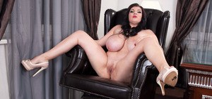 Chubby brunette Maya Milano reveals her huge tits as she strips in her office