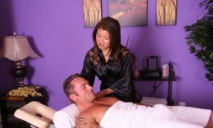 Asian massage parlor worker gives a tug job to a client in the nude