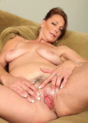 Mature lady Mimi Moore pets her pussy after teasingly removing her clothes