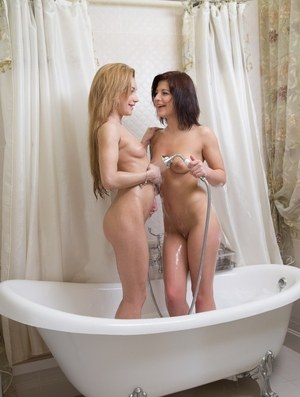 Coeds Angelin Joy and Sonya Sweet rub up against each other in a soapy bathtub