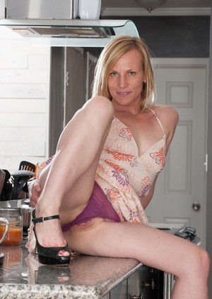 Mature woman Cody Hunter strips off her dress and panties on kitchen counter