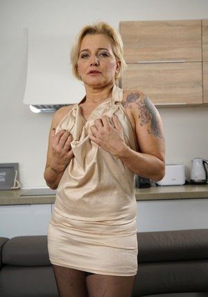 Tattooed grandmother exposes her big tits as she removes her dress