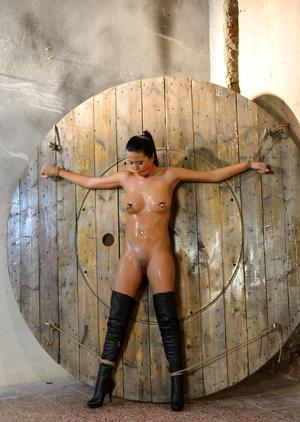 Mia Manatote is restrained to a wooden wall before painful nipple pegging