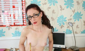 Older lady shows of her snatch atop her desk wearing glasses and stockings