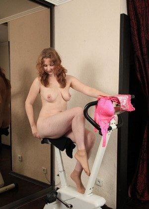 Older woman hops off her exercise bike and strips for nude poses