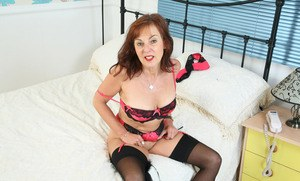 Older lady Georgie shows off her vagina attired in black stockings and heels