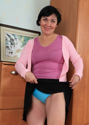 Older woman with short hair and a couple extra kilos strips naked