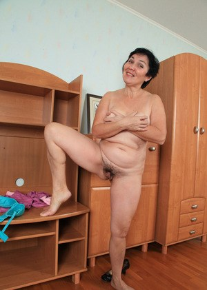 Mature lady with short hair takes off her clothes and puts a smile on her face