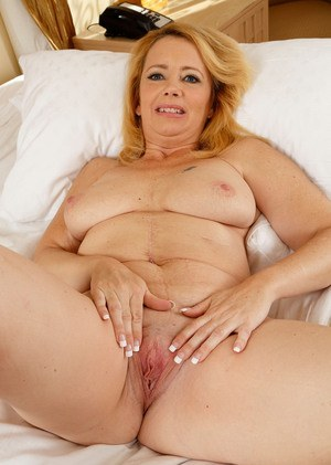 Chubby mature lady Brandie Sweet tugs on her labia lips after lingerie removal