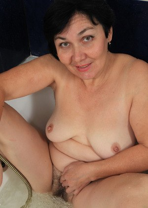 Mature woman gets naked to take a bath and play with her hairy snatch