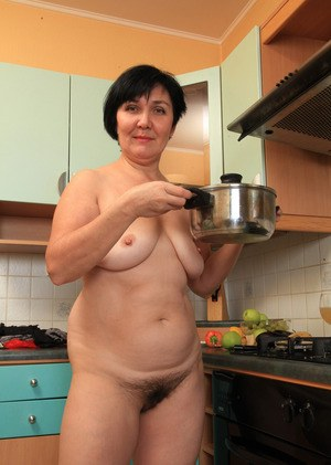 Short haired older lady plays with her beaver while preparing something to eat