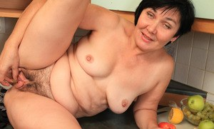 Overweight mature woman can't resist playing with her bush in the kitchen