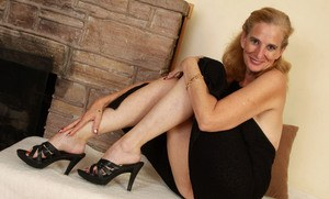 Older woman slips off her her heels and dress for nude posing