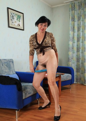 Mature woman Yulya showcases her hairy muff after undressing