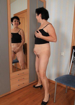 Mature woman admires herself in mirror as she undresses for nude posing