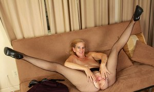 Mature lady goes about showing off her bald pussy in mesh pantyhose