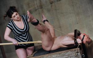 Ball gagged female slave is forcefully masturbated by a dyke in the stocks