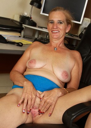 Mature woman hikes up her skirt on way to showing her pink twat in her office