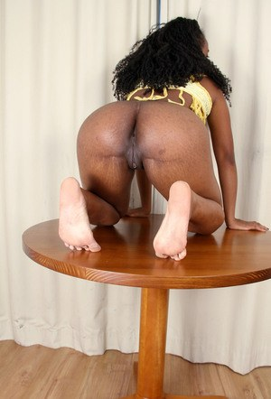 Ebony amateur shows off the pink of her vagina atop a round table