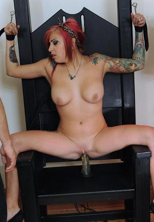Tattooed redhead is impaled upon a dildo in bondage chair