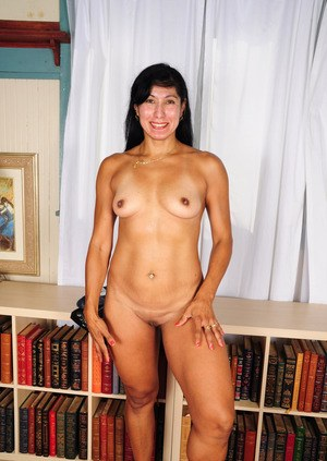 Older woman uncovers her tiny boobs as she gets naked on a book stack