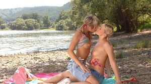 Teen girls spread a blanket on rocky shore in order to have lesbian sex