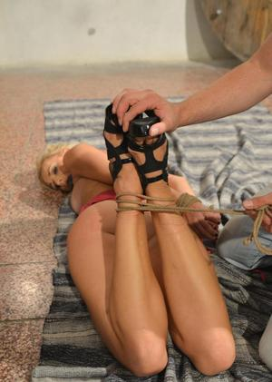 Blonde female is left ball gagged and hogtied on a blanket on cellar floor