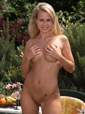 Cute amateur girl with blonde hair toys her wet pussy in the backyard