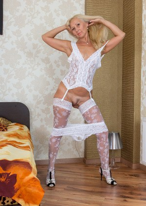 Older blonde lady Callidica strikes sexy poses in white stockings