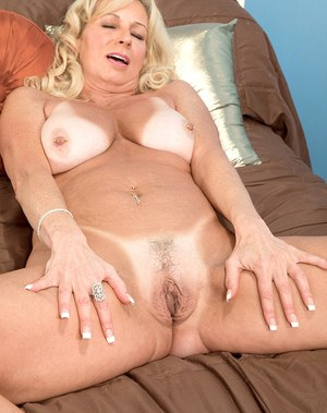Middle aged blonde Nikki Chevious lets out her big tits as she gets undressed