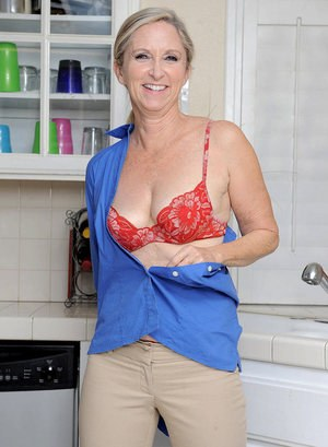 Mature lady Ann Brady wets her shaved pussy over the kitchen sink